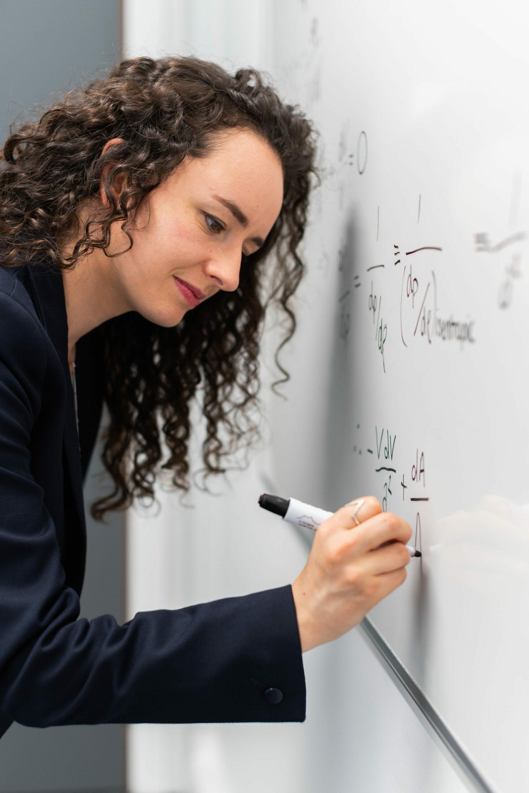 professeur écrivant des maths au tableau