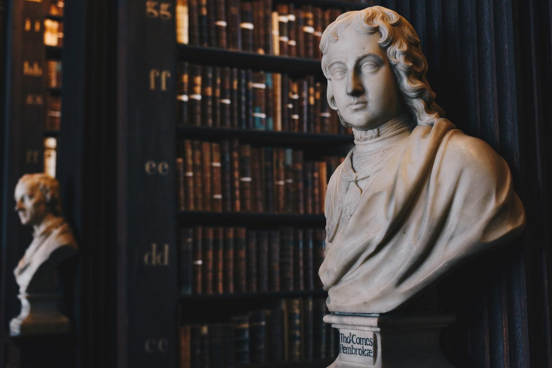 bibliothèque avec des statues de philosophe