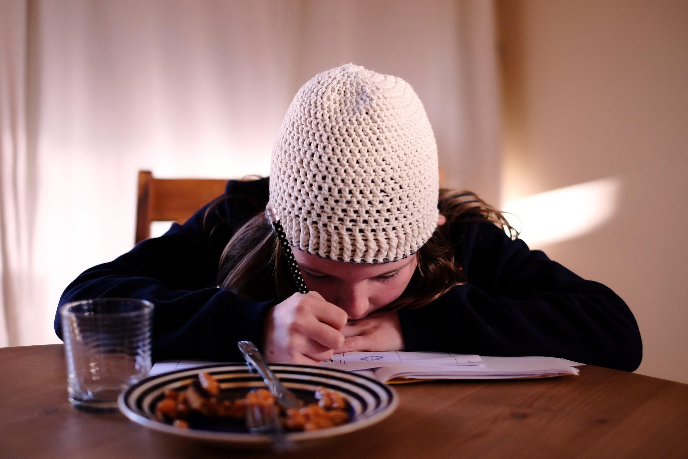 enfant faisant ses devoirs de français devant son goûté