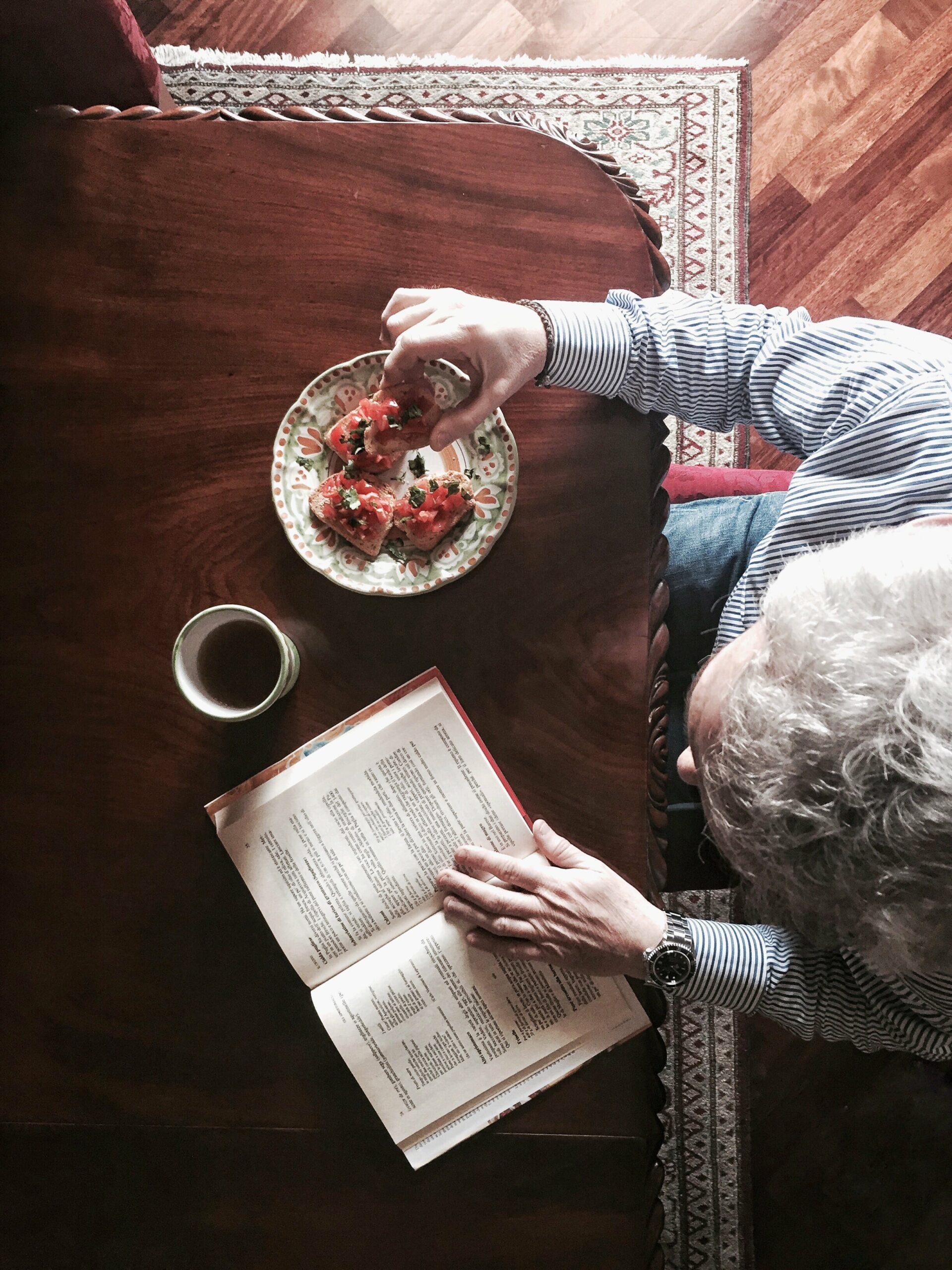 adulte lisant un livre de français à table