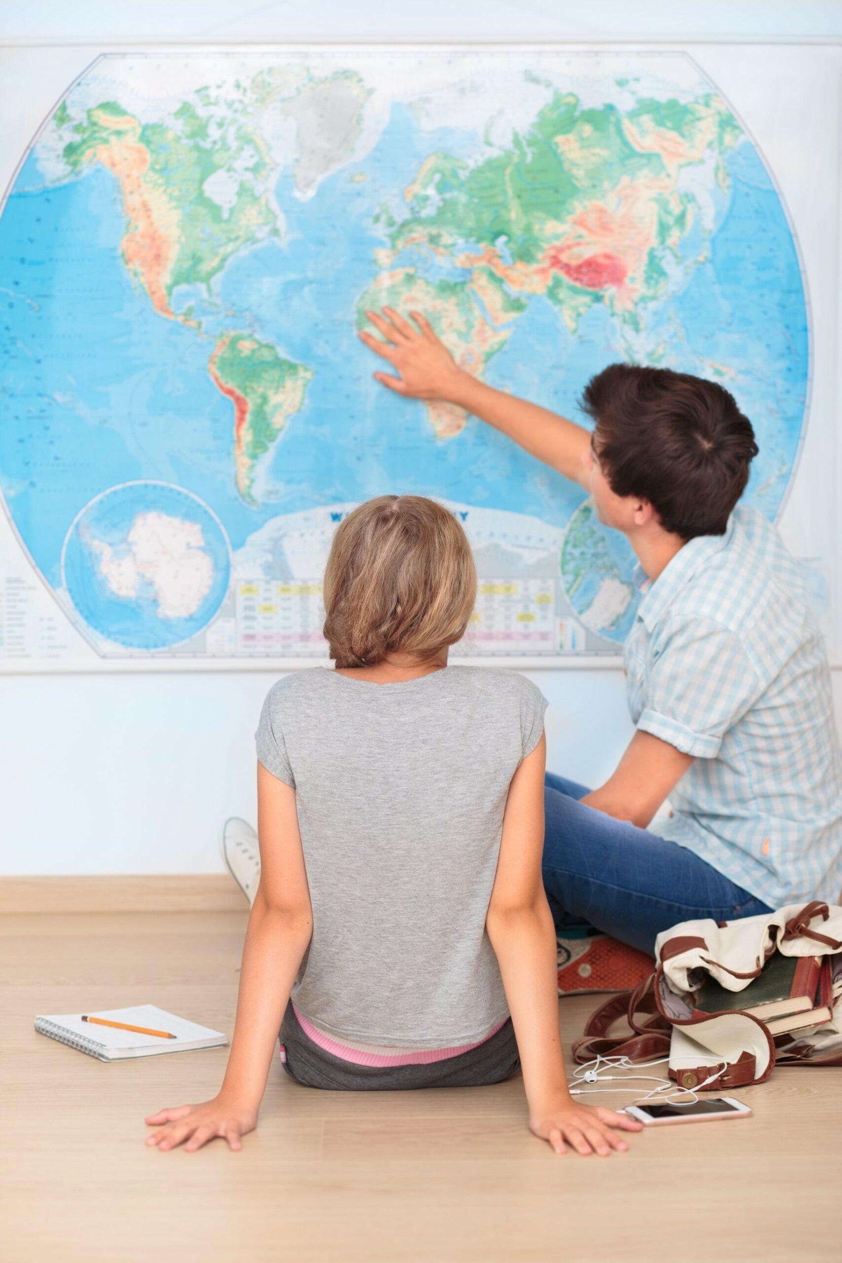 élèves travaillant sur une carte de géographie affichée au tableau