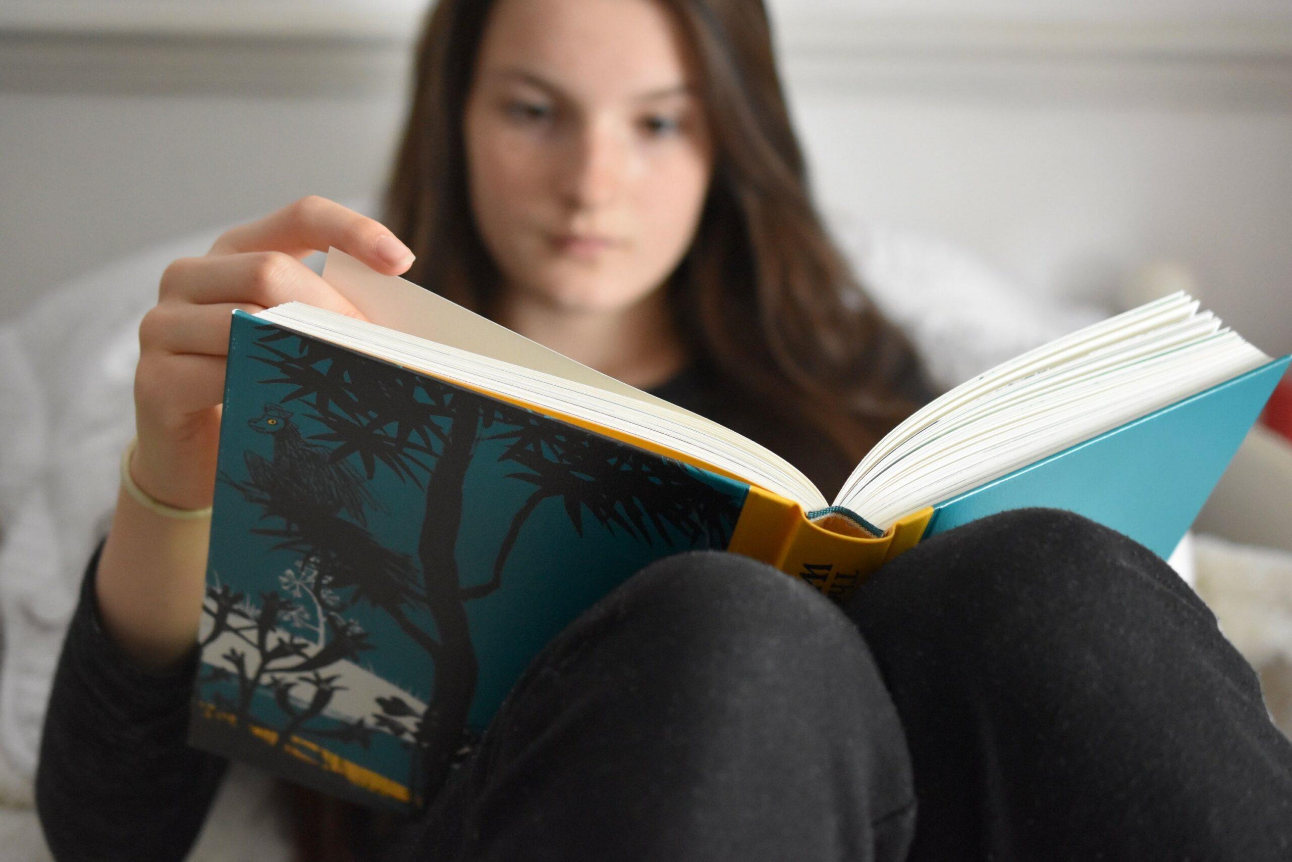 jeune fille lisant un livre d'exercices