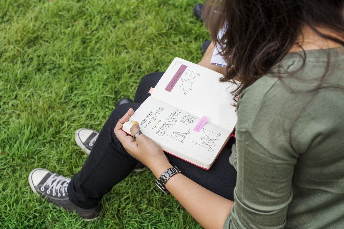 jeune femme travaillant ses devoirs dehors dans l'herbe