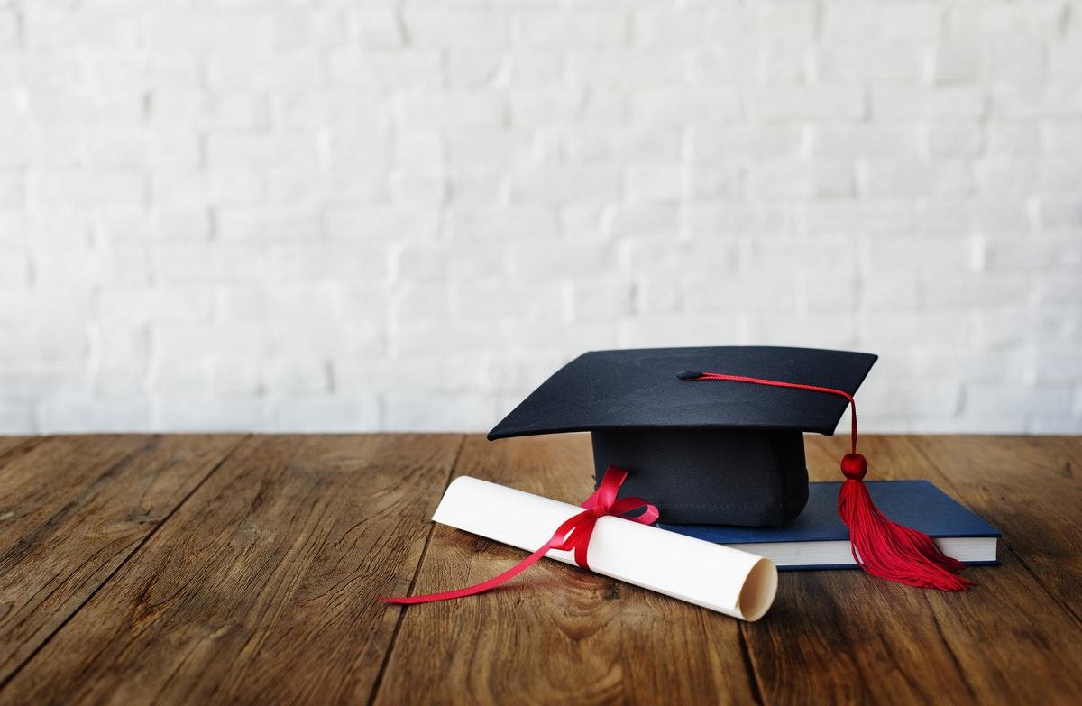 un diplôme du brevet sur une table avec un chapeau et un livre