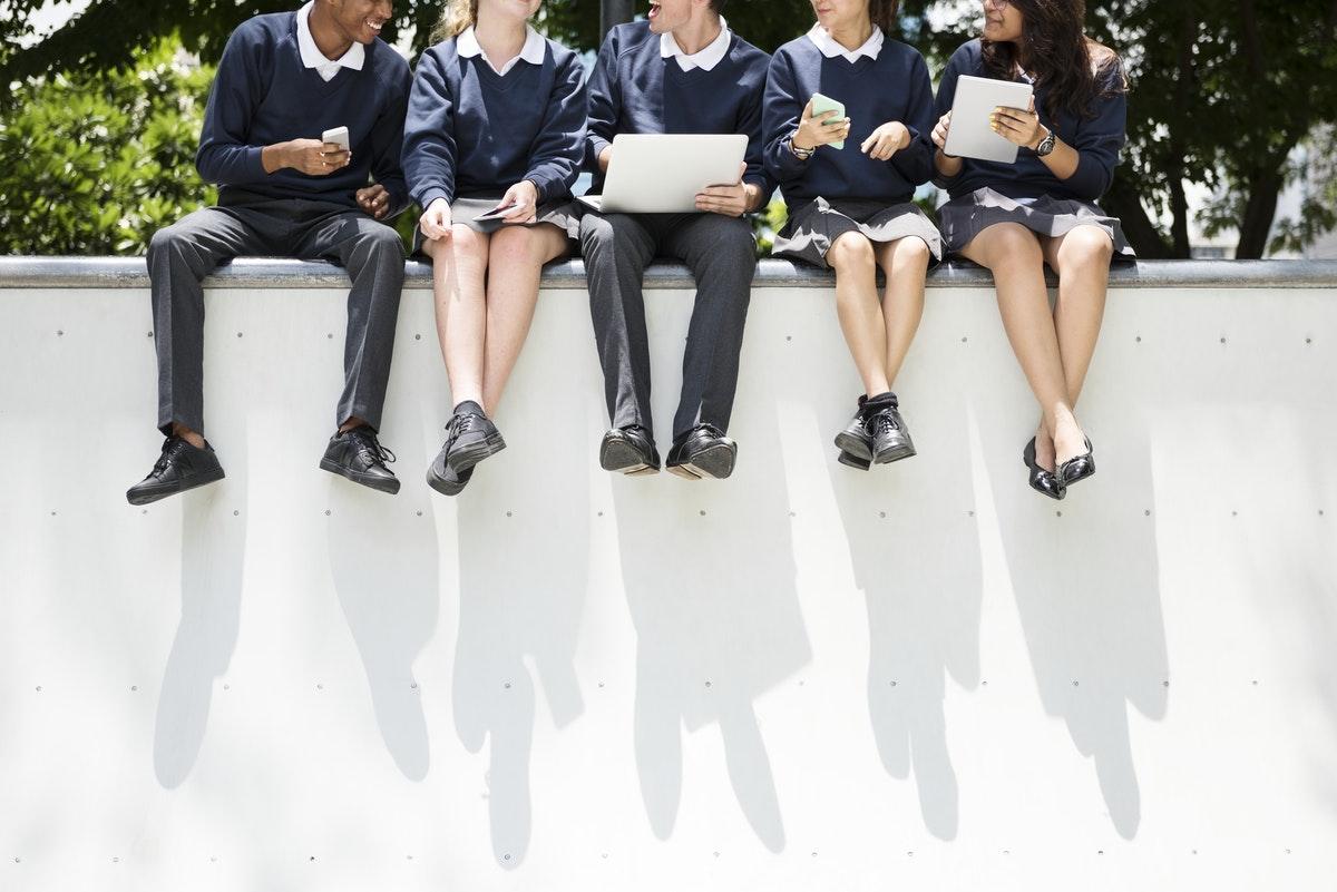 des élèves de lycée en train de travailler ainsi sur un muret