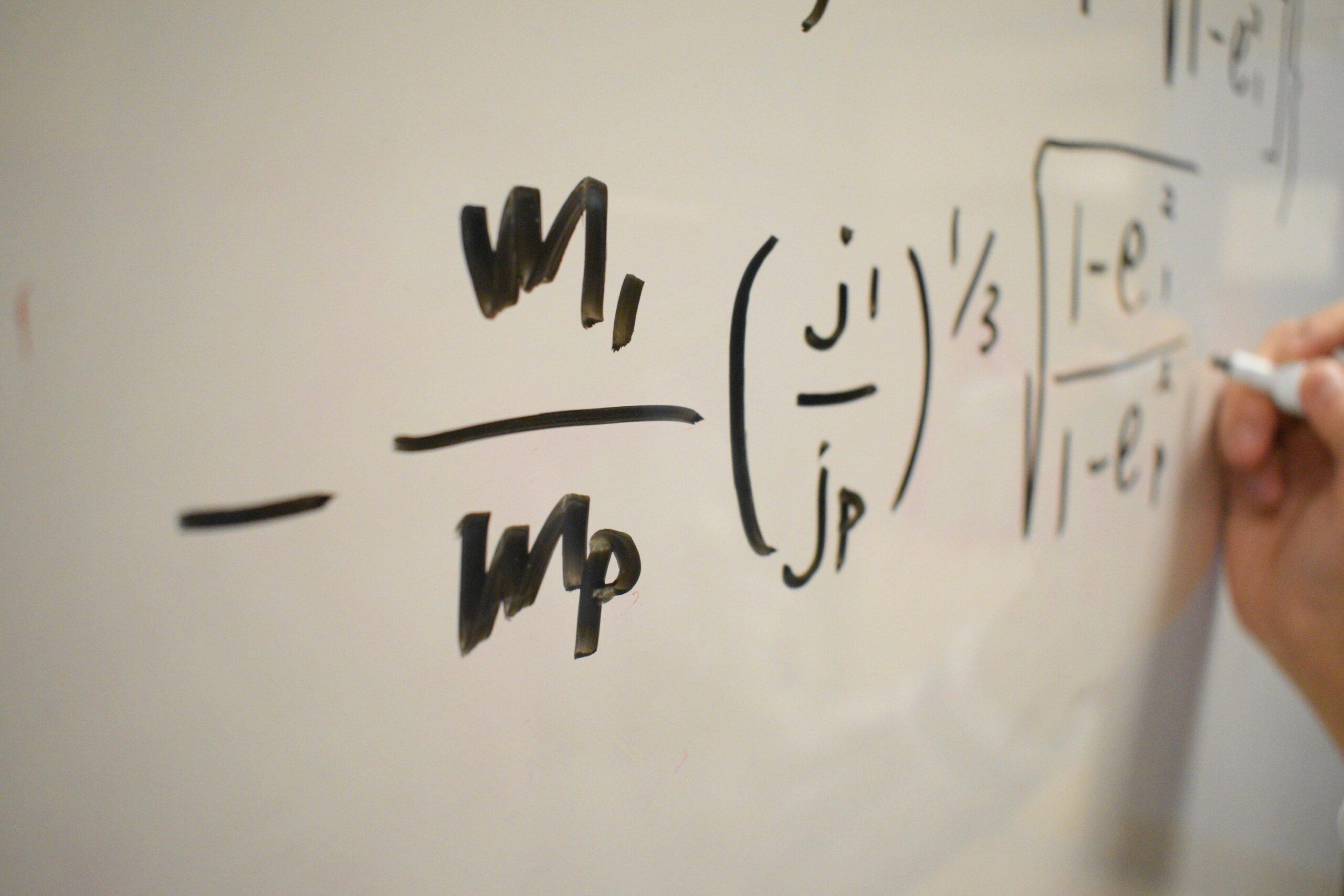 des formules mathématiques écrites sur un tableau par un professeur