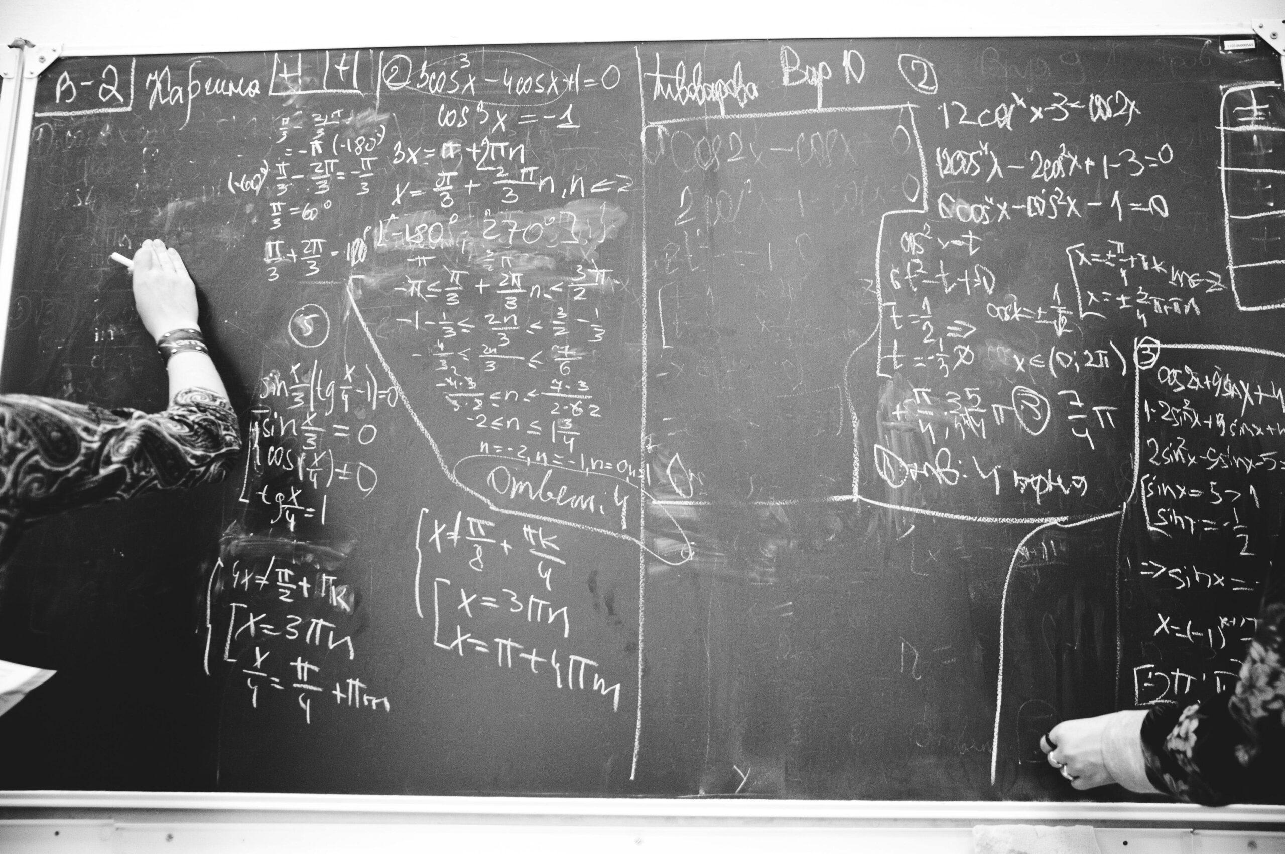 un tableau noir avec des formules mathématiques écrites à la craie