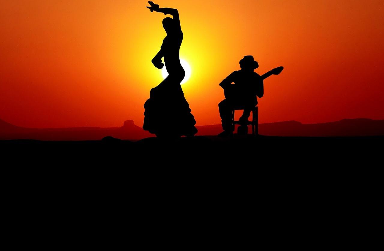 une danseuse espagnole de Flamenco ainsi qu'un joueur de guitare espagnole devant un couché de soleil