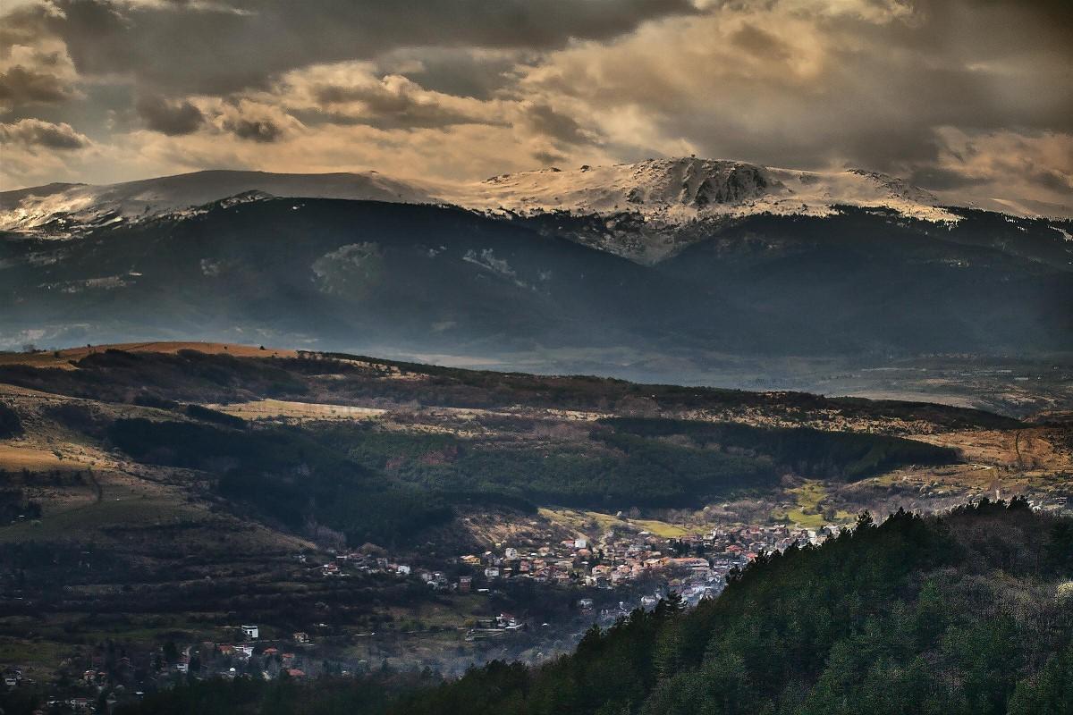 un petit village logé dans une vallée boisée entre deux montagnes