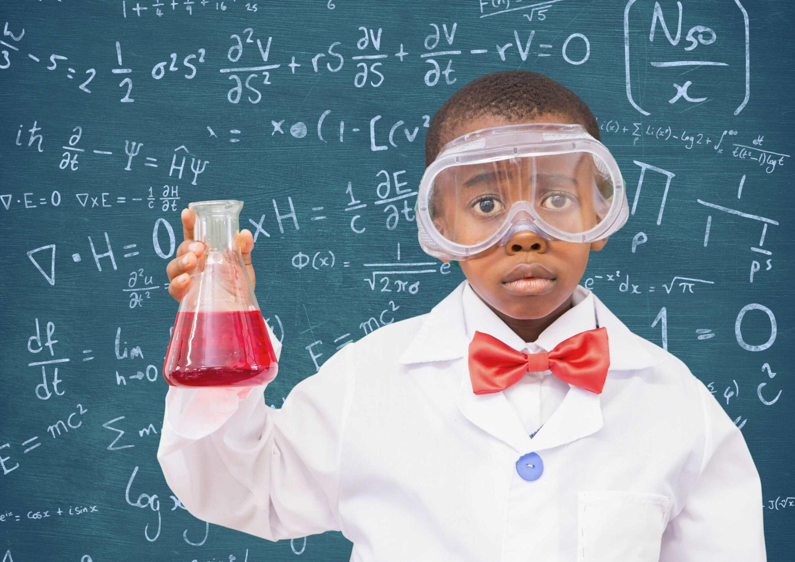 un jeune garçon en tenue de scientifique devant un tableau avec des formules mathématiques